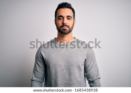 Young handsome man with beard wearing casual sweater standing over white background Relaxed with serious expression on face. Simple and natural looking at the camera.