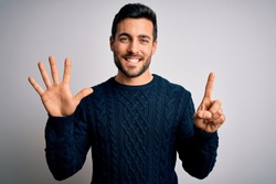 Young handsome man with beard wearing casual sweater standing over white background showing and pointing up with fingers number six while smiling confident and happy.