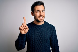 Young handsome man with beard wearing casual sweater standing over white background showing and pointing up with finger number one while smiling confident and happy.