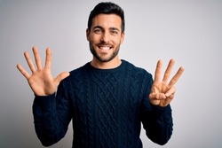 Young handsome man with beard wearing casual sweater standing over white background showing and pointing up with fingers number eight while smiling confident and happy.