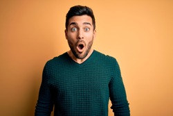 Young handsome man with beard wearing casual sweater standing over yellow background afraid and shocked with surprise expression, fear and excited face.