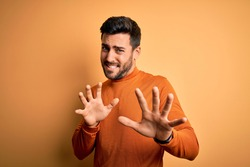 Young handsome man with beard wearing casual sweater standing over yellow background disgusted expression, displeased and fearful doing disgust face because aversion reaction. With hands raised