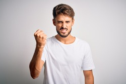 Young handsome man with beard wearing casual t-shirt standing over white background angry and mad raising fist frustrated and furious while shouting with anger. Rage and aggressive concept.