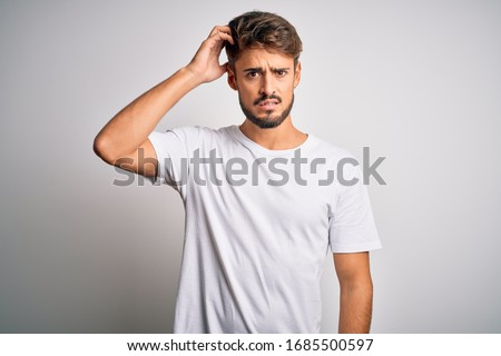 Young handsome man with beard wearing casual t-shirt standing over white background confuse and wonder about question. Uncertain with doubt, thinking with hand on head. Pensive concept.