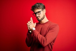 Young handsome man with beard wearing glasses and sweater standing over red background Holding symbolic gun with hand gesture, playing killing shooting weapons, angry face