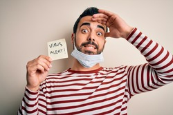Young handsome man with beard wearing medical mask holding virus alert reminder stressed with hand on head, shocked with shame and surprise face, angry and frustrated. Fear and upset for mistake.