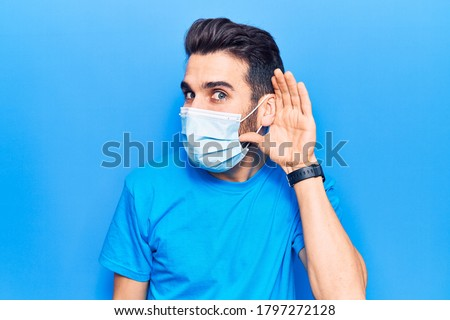 Young handsome man with beard wearing medical mask smiling with hand over ear listening and hearing to rumor or gossip. deafness concept.  ストックフォト ©