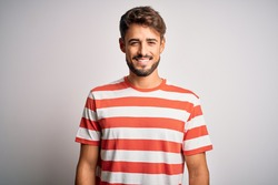Young handsome man with beard wearing striped t-shirt standing over white background with a happy and cool smile on face. Lucky person.