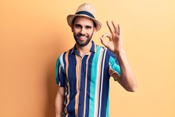 Young handsome man with beard wearing summer hat and shirt smiling positive doing ok sign with hand and fingers. successful expression.