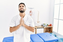 Young handsome man with beard working at pain recovery clinic begging and praying with hands together with hope expression on face very emotional and worried. begging.