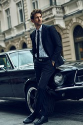 Young handsome man with black classic car wearing black suit with hands in pocket