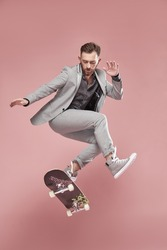Young handsome man with brown hair and beard, wearing light grey suit and sneakers, jumping with the skateboard on light pink background