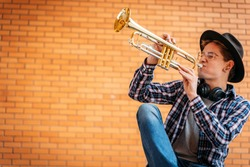Young handsome man with eye glasses and hat poses with trumpet outdoor with brick wall
