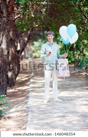 Young handsome man with gift and balloons. Gift Delivery