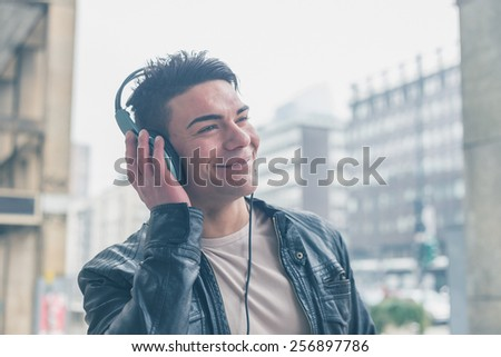 Young handsome man with headphones listening to music in the city streets #256897786