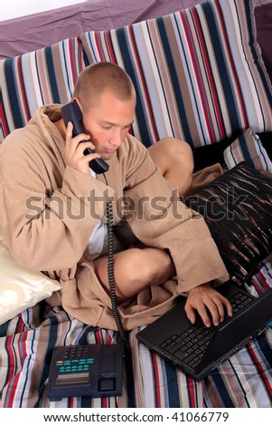 young handsome man   with laptop on bed in bedroom, making phone call.  Studio. - stock photo