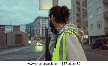 Young handsome man with long hair and beard wearing warning vest