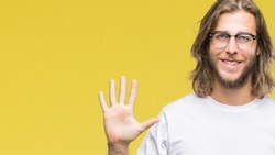 Young handsome man with long hair wearing glasses over isolated background showing and pointing up with fingers number five while smiling confident and happy.