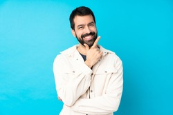 Young handsome man with white corduroy jacket over isolated blue background smiling