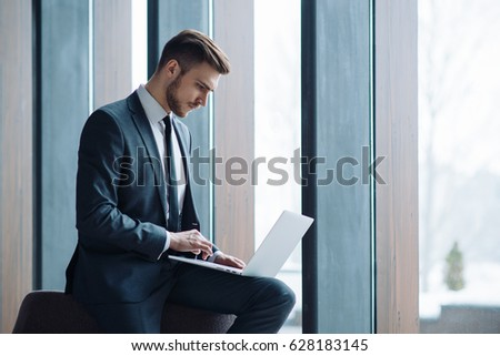 Young handsome man working in the office of mobile network company, adapting tariff plans to users need. Consultant providing service online with notebook. Business running through mobile systems.  #628183145