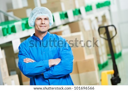 young handsome medical warehouse worker man in front of boxes with medcine drugs stack arrangement
