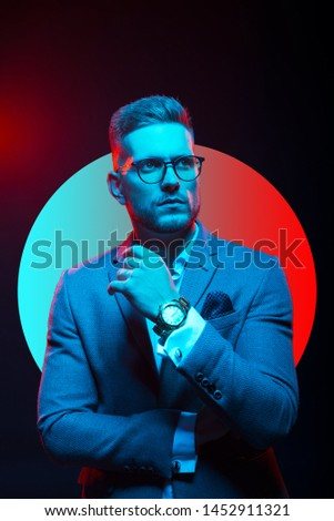 Young handsome model posing in a studio in a trendy neon light. Fashionable man in a stylish suit. Vibrant color. Bright colorful light effects. Disco style. Overlay. Gel filter. Supersaturated #1452911321