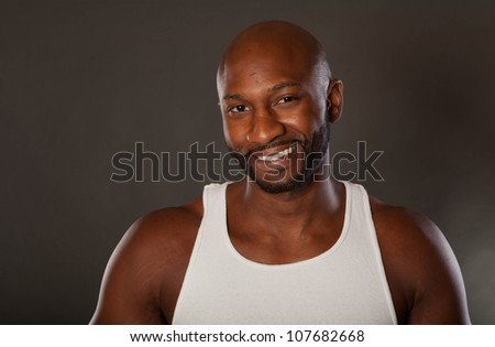 Young, handsome, muscular black man in a t-shirt smiling looking at the camera