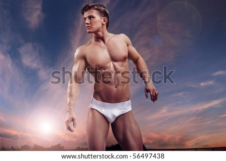Young handsome muscular guy over twilight sky