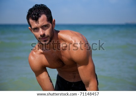 Young handsome muscular man getting up from the water looking at camera. - stock photo