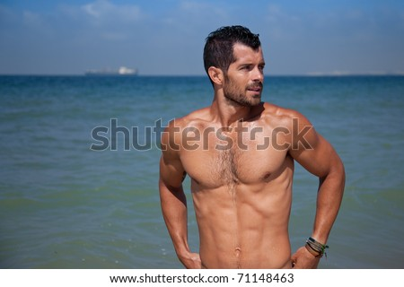 Young handsome muscular man standing in blue water looking away.