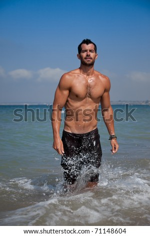 Young handsome muscular man walking out of the water in a tropical beach wearing a bathing suit