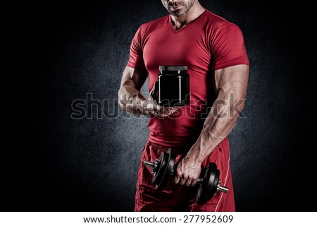 young handsome muscular man with a sports nutrition and dumbbells in the hands of
