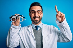 Young handsome optical man with beard holding optometry glasses over blue background smiling amazed and surprised and pointing up with fingers and raised arms.