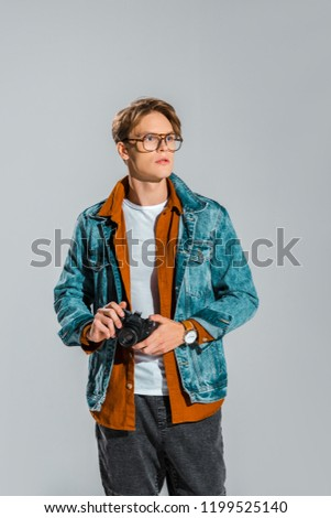 young handsome photographer holding camera isolated on grey