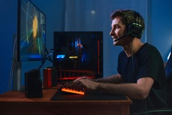 Young handsome pro gamer playing in online video game on computer at home using headphones and microphone for talking with his team, smiling, enjoying the play. Side view. Cybersport concept