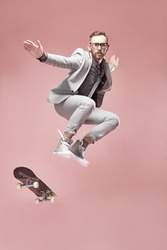 Young handsome serious man with glasses, brown hair and beard, wearing light grey suit and sneakers, jumping with the skateboard and flying in the air on light pink background