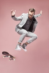 Young handsome serious man with glasses, brown hair and beard, wearing light grey suit and sneakers, jumping with the skateboard and flying on light pink background