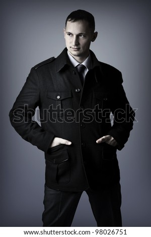 Young handsome sexy elegant business man in black coat - stock photo