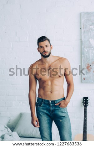 young handsome shirtless man with muscular torso posing in bedroom at home
