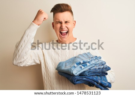 Young handsome shopkeeper man holding folded jeans over isolated white background annoyed and frustrated shouting with anger, crazy and yelling with raised hand, anger concept