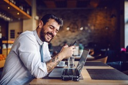 Young handsome smiling caucasian tattooed elegant businessman in shirt and tie using smart phone while sitting in cafe. On table is laptop.