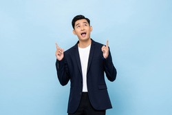 Young handsome southeast Asian businessman pointing hands and looking upward on light blue studio background