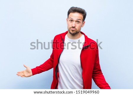 young handsome sports man or monitor feeling clueless and confused, having no idea, absolutely puzzled with a dumb or foolish look against flat wall