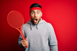 Young handsome sportsman holding tennis racket wearing sportswear over red background scared in shock with a surprise face, afraid and excited with fear expression