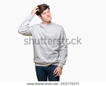 Young handsome sporty man wearing sweatshirt over isolated background confuse and wonder about question. Uncertain with doubt, thinking with hand on head. Pensive concept.
