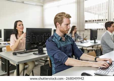 Young handsome student using computer in classroom