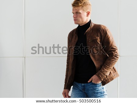 Young handsome stylish man in brown jacket in autumn time outdoor in casual style #503500516