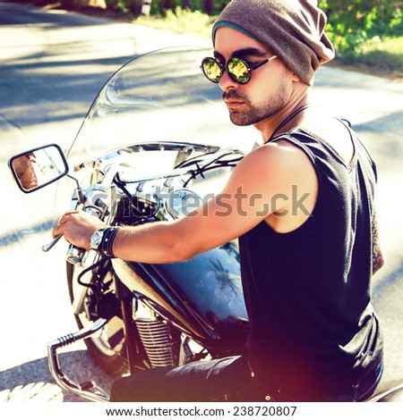 Young handsome stylish man riding bike, wearing hat and sunglasses, brutal rock n roll style. Instagram bright colors.