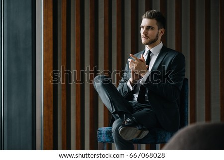 Young handsome successful boss sitting in a leather armchair in luxury fashionable interior thinking about his plans of future development of his worldwide well-known digital marketing company.