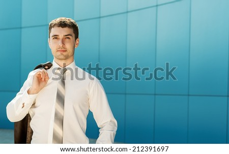 Young handsome successful bussiness man in suit speaking over the phone